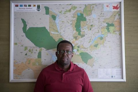 Dr Nyambe Nyambe, executive director of the Kavango-Zambezi Transfrontier Conservation Area, stands in front of a map showing the vast region affected by elephant overpopulation - Credit: Eddie Mulholland