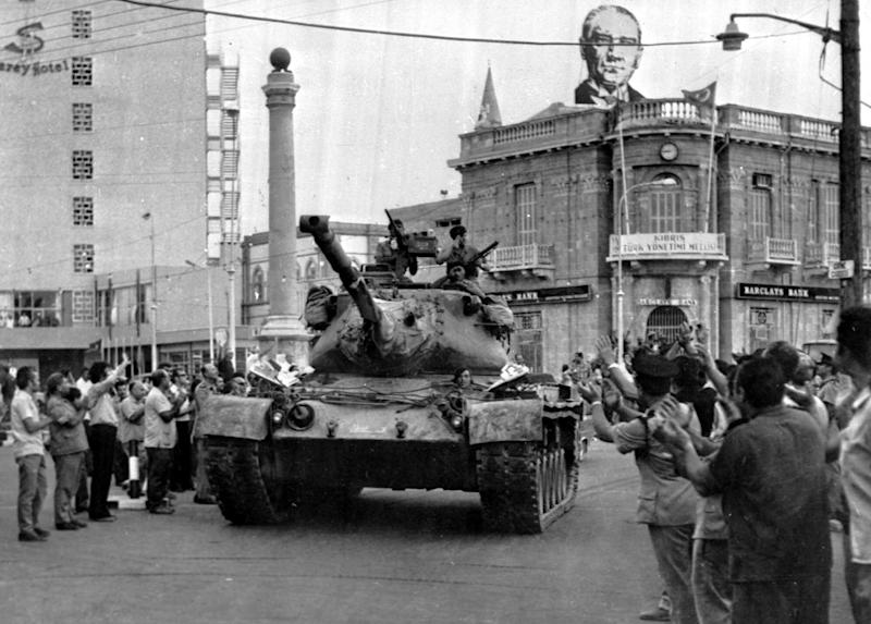 FILE - In this on July 24, 1974 file photo a Turkish army tank passes the Saray Hotel in the Turkish section of Nicosia, Cyprus, On the roof of a nearby building is a picture of Kemal Ataturk, founder of the modern Turkish republic. The 1974 invasion was sparked by an abortive coup by supporters of union with Greece. It led to the occupation by Turkey of the northern third of Cyprus and some 200,000 Greek Cypriots fleeing or being expelled from their homes in the north. The current spat between the EU and Russia over the future of its economy underlines the small Mediterranean island has played an outsized role in history. (AP Photo, File)