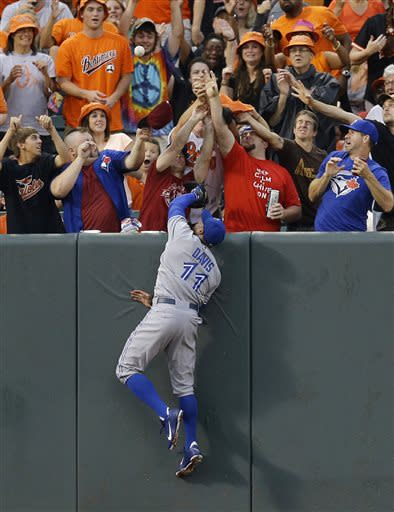 Toronto Blue Jays left fielder Rajai Davis and fans reach for a ball hit for a two-run home run by Baltimore Orioles' Chris Davis in the second inning of a baseball game, Friday, July 12, 2013, in Baltimore. (AP Photo/Patrick Semansky)