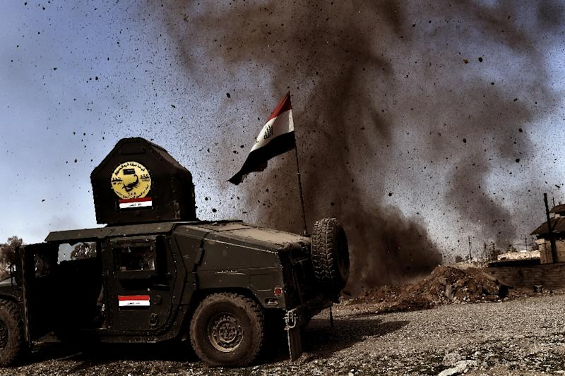 An explosion hits near a vehicle belonging to Iraq's elite Rapid Response Division on February 25, 2017, during the assault to retake the western half of Mosul, which is still occupied by Islamic State group jihadists (AFP Photo/ARIS MESSINIS)