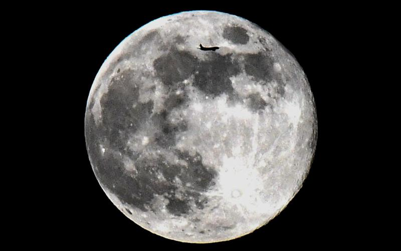 A plane flies past the full moon in Moscow on April 19, 2019 - AFP