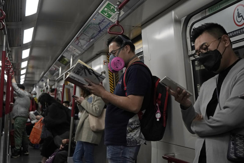 People wear masks on a subway train in Hong Kong, Tuesday, March 3, 2020. (AP Photo/Kin Cheung)