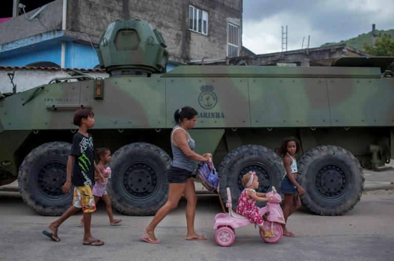 A woman and kids walks past an armored vehicle during an army operation in a crime-plgued favela in Rio de Janeiro
