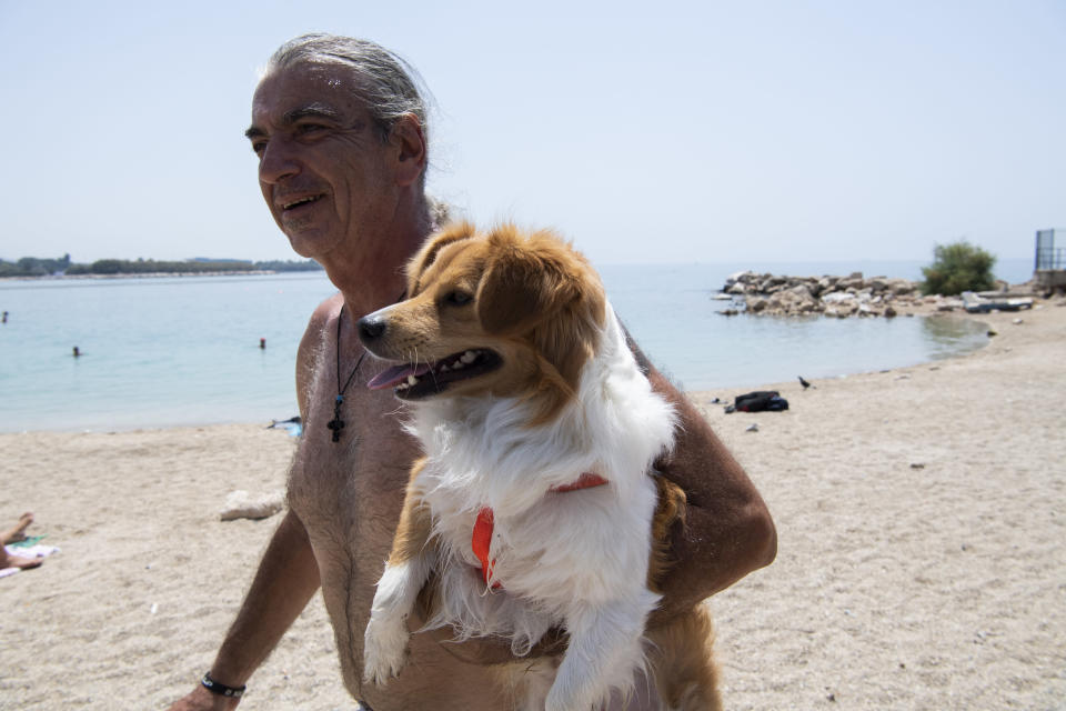 A man carries his dog during a heatwave at a beach, in Alimos suburb, southern Athens, Greece, Monday, Aug. 2, 2021. The heat wave is expected to peak Monday, with temperatures inland ranging from 42 to 46 degrees Celsius (107.6 to 114.8 Fahrenheit). Temperatures will remain at 40 Celsius (104 Fahrenheit) or above in much of Greece until at least Friday, meteorologists say. (AP Photo/Michael Varaklas)