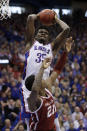 Kansas center Udoka Azubuike (35) rebounds over Oklahoma forward Kristian Doolittle (21) during the first half of an NCAA college basketball game in Lawrence, Kan., Saturday, Feb. 15, 2020. (AP Photo/Orlin Wagner)