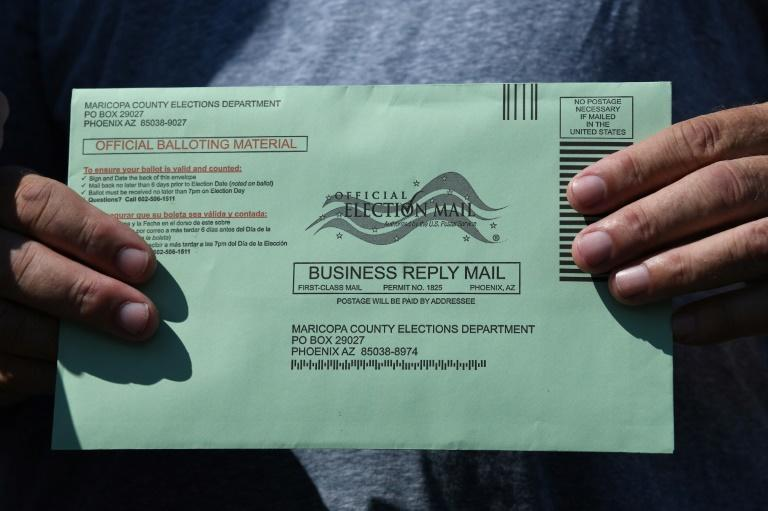 "A voter holds a green envelope containing their ballot in Arizona, where it already ""looks like election day"""