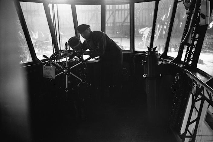 <p>A crewman inside the cockpit of the Hindenburg airship seen while in the hangar. (Corbis via Getty Images) </p>
