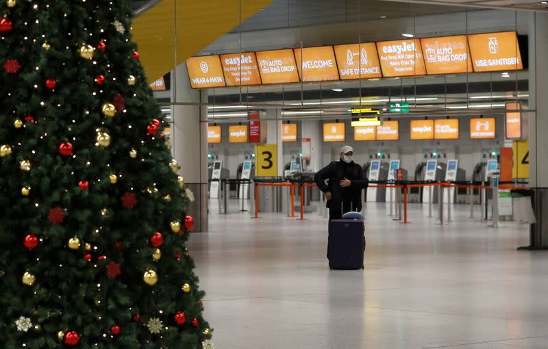 A passenger stands in an almost empty check-in area at Gatwick Airport, amid the coronavirus disease (COVID-19) outbreak, in Crawley