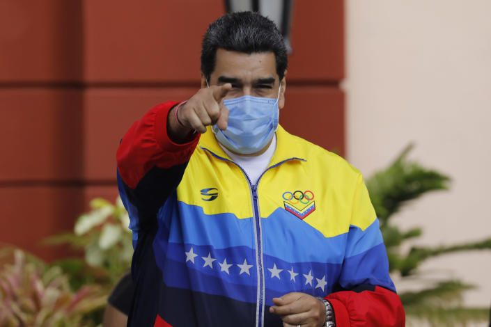 Venezuelan President Nicolas Maduro points to supporters during an event marking Youth Day at Miraflores presidential palace in Caracas, Venezuela, Friday, Feb. 12, 2021, amid the COVID-19 pandemic. The annual holiday commemorates young people who accompanied heroes in the battle for Venezuela's independence. (AP Photo/Ariana Cubillos)