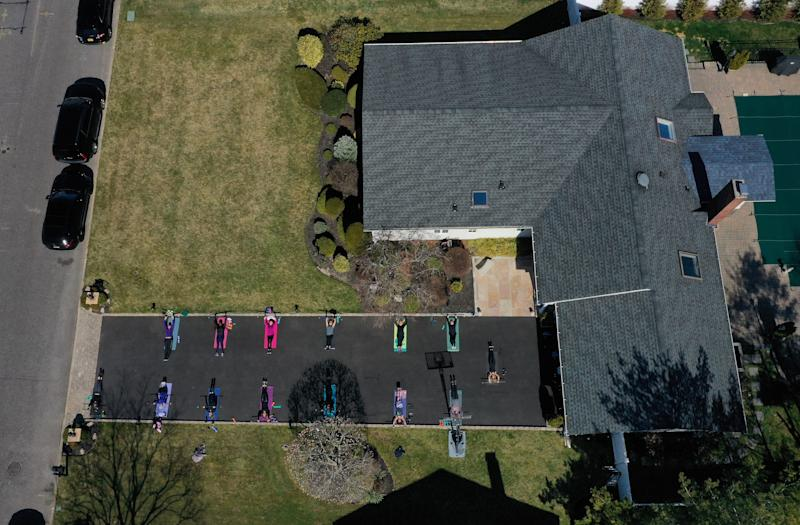 In Long Island, New York, a fitness instructor leads an exercise class in her driveway. She is an instructor at three gyms in her area but they are closed due to the coronavirus pandemic. (Photo by Al Bello/Getty Images)