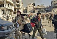 Syrian pro-government forces are seen in front of damaged buildings in the eastern city of Deir Ezzor on November 3, 2017