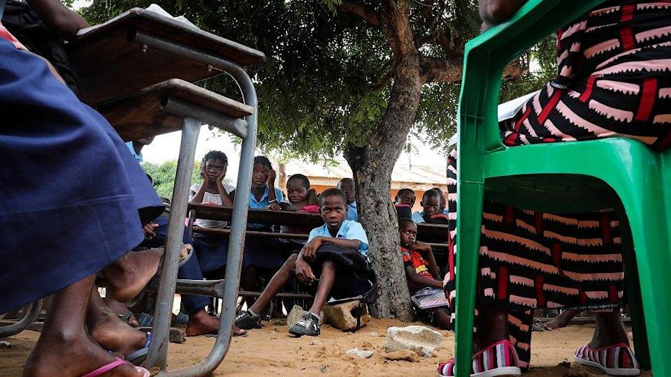 A teacher gives a lesson to the students at the open-air classes at the primary school in the neighborhood of Mahate, in Pemba