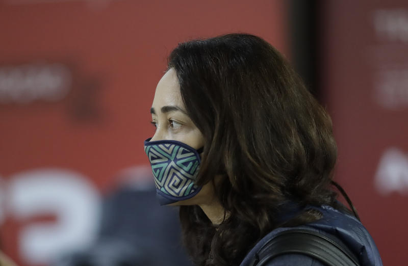 A woman uses a sleep mask over her mouth as a precaution against the spread of the new coronavirus COVID-19 after her flight landed at the Sao Paulo International Airport in Sao Paulo, Brazil, Thursday, Feb. 27, 2020. (AP Photo/Andre Penner)