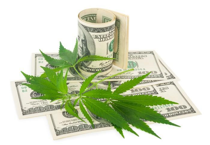Cannabis leaves on top of one hundred dollar bills.