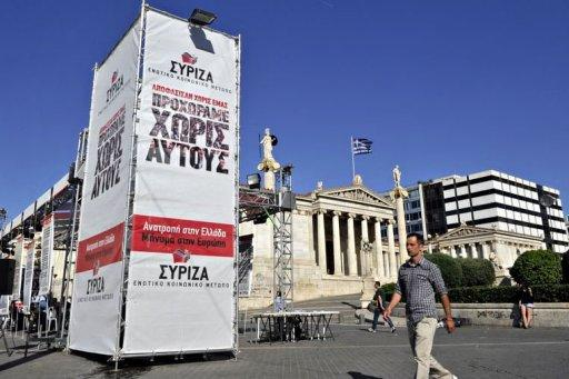 People walk by the main election campaign kiosk of the Communists and leftist Syriza party ahead of the May 6 elections