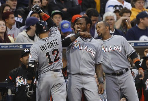 Miami Marlins' Omar Infante celebrates with teammates after driving in a run against the San Diego Padres with a sacrifice fly during eighth inning of a baseball game Saturday, May 5, 2012 in San Diego. (AP Photo/Lenny Ignelzi)