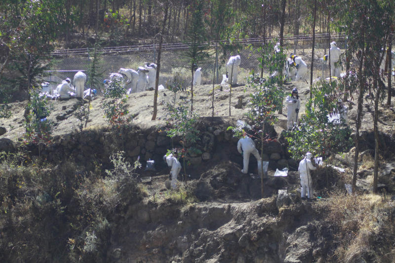 In this July 31, 2012 photo, workers at the Antamina copper mine, wearing white uniforms, clean the river in Cajacay, Peru.  A pipeline carrying copper concentrate laced with volatile compounds burst open on July 25.  Three weeks after the leak spilled 45 tons of slurry into the town of Cajacay, spreading toxic dust that left 42 people hospitalized for up to 11 days, the copper mine's owner, Antamina, has said little about the accident, and been silent about the slurry's chemistry. (AP Photo/La Republica Newspaper)