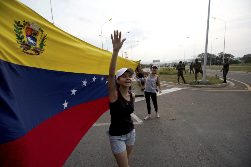 "Woman shouts ""Welcome humanitarian aid"" as he waives Venezuelan flag in front aof a group of Venezuelan Army soldiers and National Guard officers blocking the main access to the Tienditas International Bridge that links Colombia and Venezuela, near Urena, Venezuela, Thursday, Feb. 7, 2019. Venezuela's opposition leaders requested the shipments and vowed to bring them inside the troubled nation despite objections from embattled President Nicolas Maduro. (AP Photo/Fernando Llano)"