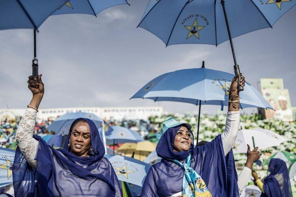 Two women dressed in matching pro-ruling party outfits also carry matching umbrellas which they are lifting up.