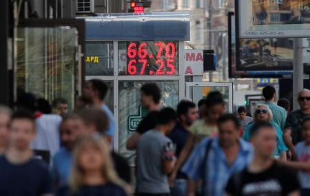 Pedestrians walk by an electronic board showing currency exchange rates of the U.S. dollar against Russian rouble in Moscow, Russia August 10, 2018. REUTERS/Maxim Shemetov