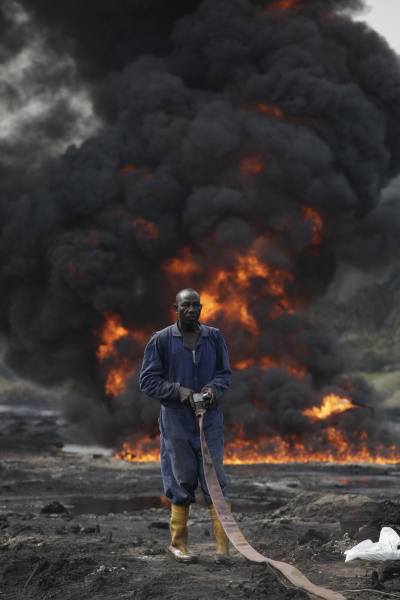 A firefighter handles a hose a they try to contain flames and a tower of smoke from a burning oil pipeline in Ijeododo on the outskirts of Lagos, Nigeria Thursday, Dec. 20, 2012. The oil pipeline belonging to Nigeria National Petroleum Cooperation exploded near Nigeria's largest city as thieves tried to siphon oil from it Monday. (AP Photo/Sunday Alamba)