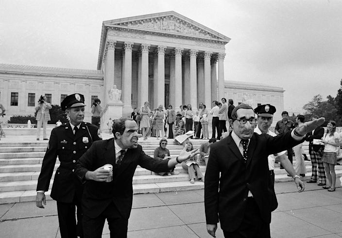 <p>Two demonstrators are escorted by police from the Supreme Court building, July 24, 1974. (Photo: John Duricka/AP) </p>