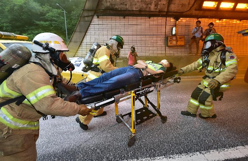 South Korean rescue personnel transport a mock victim during an anti-terror drill as part of an annual joint military drill called 'Ulchi Freedom', outside a tunnel in Seoul, in August 2014 (AFP Photo/Jung Yeon-Je)