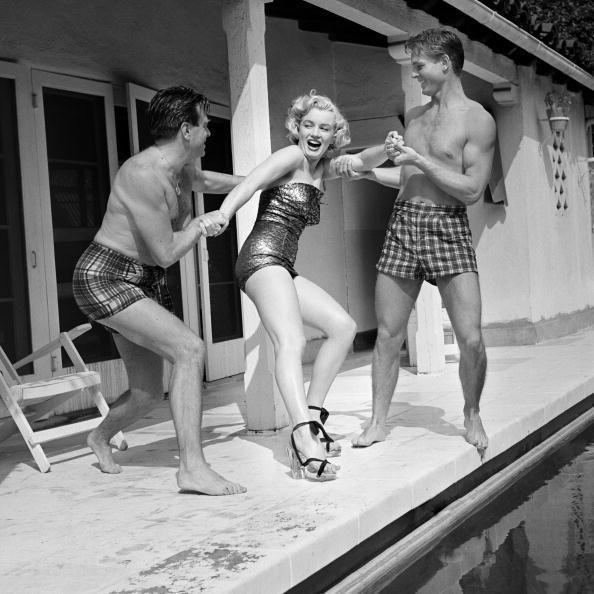 <p>Marilyn Monroe resists being thrown into the water by two male friends during a pool day in 1950. </p>