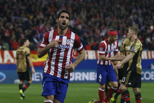 Atletico's Raul Garcia, centre, celebrates his goal during a Champions League last 16 second leg soccer match between Atletico Madrid and AC Milan, at the Vicente Calderon stadium in Madrid, Tuesday, March 11, 2014. (AP Photo/Andres Kudacki)