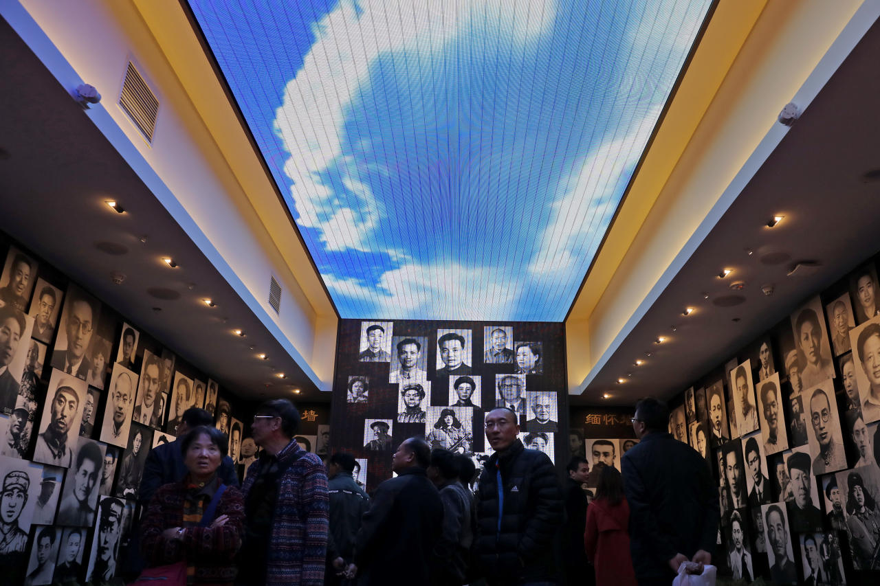 Visitors look at portraits of the past Communist Party members on display at the museum of the first National Congress of the Communist Party of China in Shanghai, China, Sunday, Nov. 19, 2017. Chinese tourists and visitors have flocked to the museum in Shanghai since President Xi Jinping made a visit with the newly-installed line-up of top party leaders late last month. During the leaders' visit, they were depicted on state television reaffirming their party oaths with their fists raised. (AP Photo/Andy Wong)