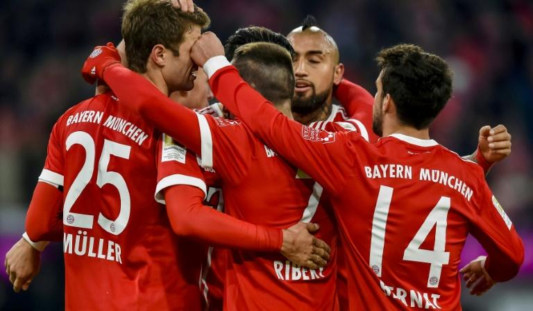 Bayern Munich's forward Thomas Mueller (L) is congratulated by teammates after he scored the team's 100th goal during a match against Werder Bremen on January 21, 2018