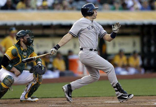 New York Yankees' Mark Teixeira, right, swings for an RBI-single off Oakland Athletics' Sonny Gray in the first inning of a baseball game on Friday, June 13, 2014, in Oakland, Calif. (AP Photo/Ben Margot)