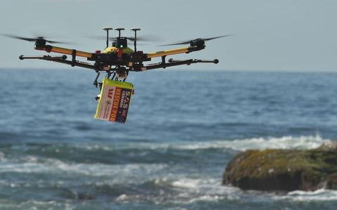 A shark-spotting drone with a safety flotation device attached underneath flying over Bilgola beach north of Sydney. - Credit: PETER PARKS/AFP