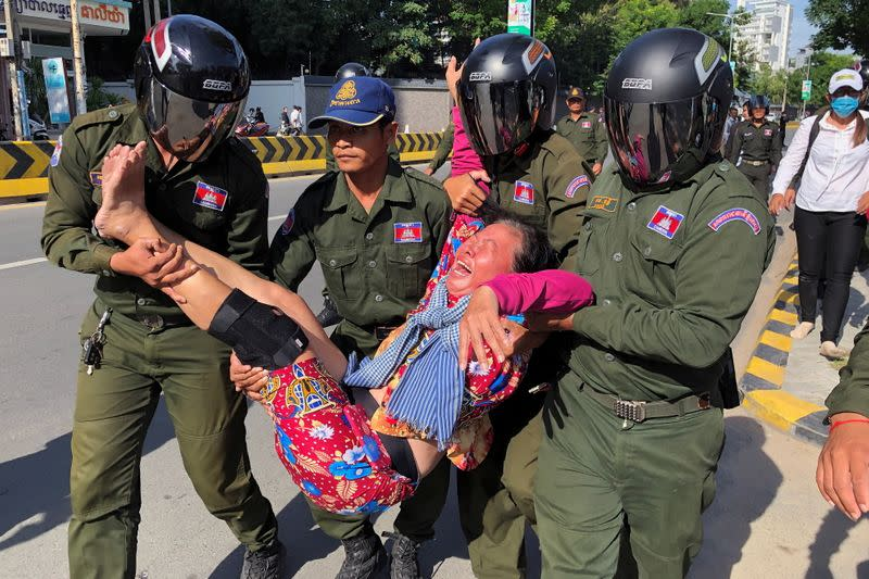 A woman is carried by police officers after security guards broke up a small protest near the Chinese embassy, in Phnom Penh