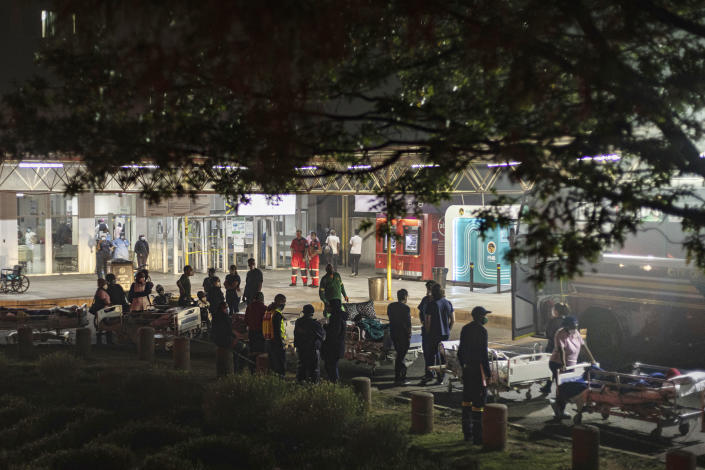 Hospital staff prepare to evacuate patients on stretchers at the Charlotte Maxeke Hospital in Johannesburg, Saturday, April 17, 2021. Patients were evacuated after a fire reignited in a dispensary almost 12 hours after it was initially reported. (AP Photo/Ali Greeff)