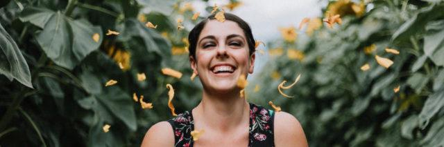 A woman laughing outside surrounded by green leaves and showered with orange flower petals
