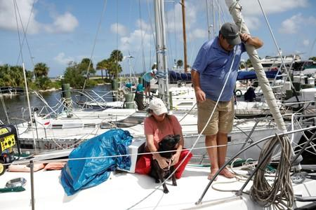 Lisa and Ned Keahey, who live in a sailboat and plan to stay aboard during Hurricane Dorian, are seen with their dog Princess Leia at a marina in Titusville