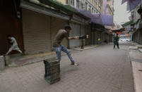 Young people play cricket at a market closed due to new restrictions announced by provincial government to help control the spread of the coronavirus, in Karachi, Pakistan, Friday, July 30, 2021. (AP Photo/Fareed Khan)