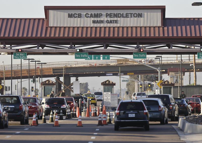 Vehicles file through the main gate of Camp Pendleton Marine Base on Wednesday, Nov. 13, 2013, at Camp Pendleton, Calif. Four Marines were reported killed Wednesday in an accident while clearing an unexploded ordnance. (AP Photo/Lenny Ignelzi)