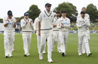 New Zealand players leave the field led by Tim Southee, center, after dismissing the West Indies for 138 runs during play on day three of their first cricket test in Hamilton, New Zealand, Saturday, Dec. 5, 2020. (Andrew Cornaga/Photosport via AP)