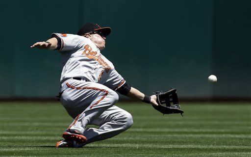 Baltimore Orioles left fielder Nate McLouth makes a sliding attempt at a pop fly from Oakland Athletics' Brandon Moss during the second inning of a baseball game, Sunday, April 28, 2013, in Oakland. Calif. Moss got a single on the play. (AP Photo/Marcio Jose Sanchez)