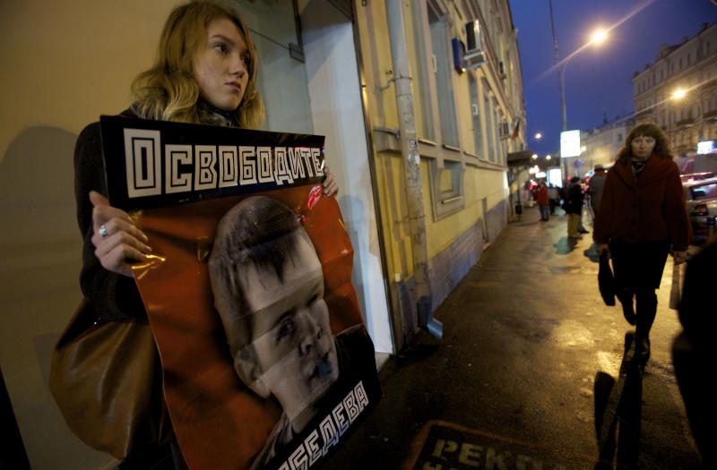 """An opposition supporter holds a poster reading """"Free Lebedev"""" near the building of a court which sanctioned the arrest of leftist activist Konstantin Lebedev in Moscow, Thursday, Oct. 18, 2012. Russia's top investigative agency filed criminal charges Thursday against Konstantin Lebedev, an assistant of opposition leader Sergei Udaltsov, continuing a widespread crackdown on the movement against President Vladimir Putin. The Investigative Committee said in a statement that Left Front member Konstantin Lebedev has been charged with plotting mass riots and could face a jail term of up to ten years. (AP Photo/Ivan Sekretarev)"""
