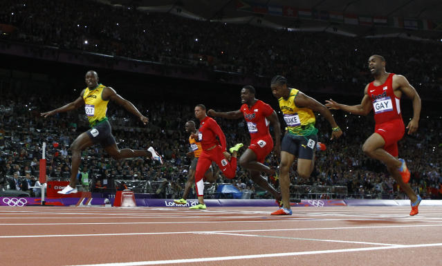 Jamaica's Usain Bolt (L) sprints ahead of the field to win the men's 100m final during the London 2012 Olympic Games at the Olympic Stadium August 5, 2012. Bolt came first ahead of compatriot Yohan Blake who finished second and Justin Gatlin of the U.S. who placed third. REUTERS/Kai Pfaffenbach (BRITAIN - Tags: SPORT ATHLETICS OLYMPICS)