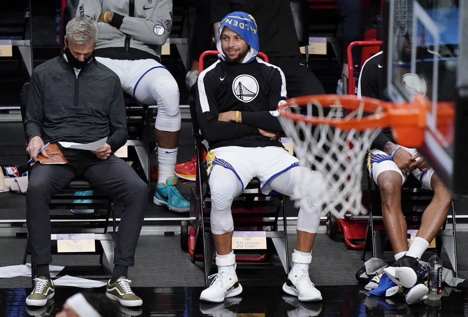 Golden State Warriors guard Stephen Curry, right, watches from the bench during the second half of an opening night NBA basketball game against the Brooklyn Nets, Tuesday, Dec. 22, 2020, in New York. (AP Photo/Kathy Willens)
