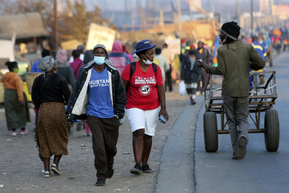 People wear face masks to protect against coronavirus in Harare, Monday, Sept. 21, 2020. As Zimbabwe's coronavirus infections decline, strict lockdowns designed to curb the disease are being replaced by a return to relatively normal life. The threat has eased so much that many people see no need to be cautious, which has invited complacency. (AP Photo/Tsvangirayi Mukwazhi)