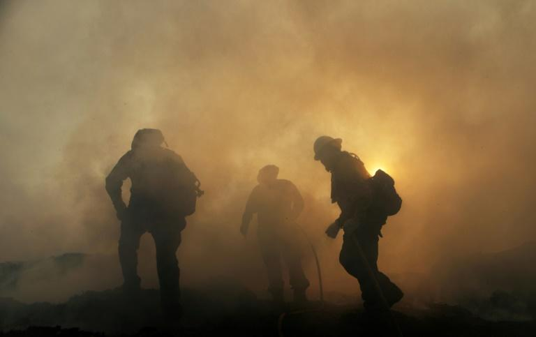 About 1,000 firefighters, backed by water-dropping helicopters and planes releasing fire retardants, fought a southern California wildfire, which began in the city of Sylmar, that forced the shutdown of several major highways