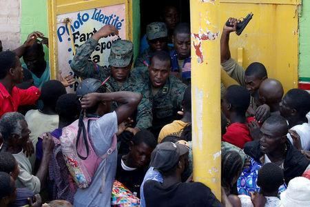 Haitian soldiers shoot in the air to try to control the crowd as they wait for food to be handed out after Hurricane Matthew hit Jeremie, Haiti, October 18, 2016. REUTERS/Carlos Garcia Rawlins/File Photo