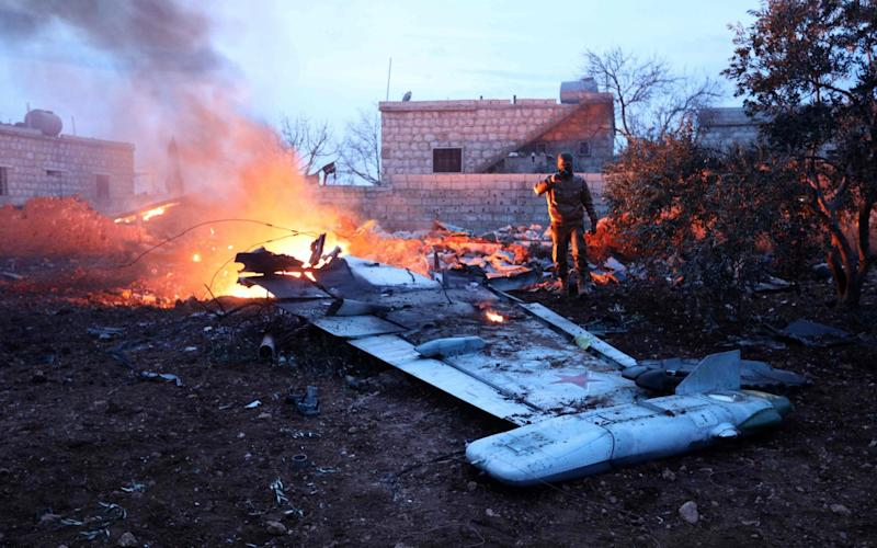 Rebel fighter taking a picture of a downed Sukhoi-25 fighter jet in Syria's northwest province of Idlib. - AFP