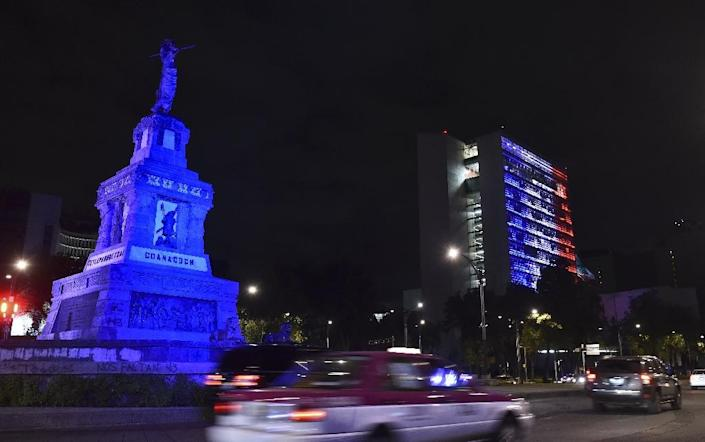The Mexican Senate building in Mexico City is illuminated with the red, white and blue colors of the French national flag on November 13, 2015 after attackers kill at least 120 people in Paris (AFP Photo/Yuri Cortez)