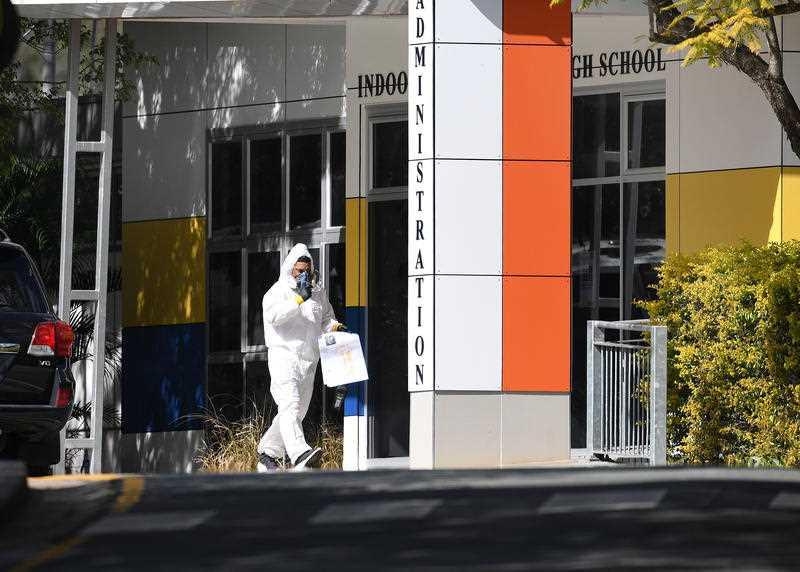 A cleaner in protective gear is seen at Indooroopilly State High School in Brisbane.